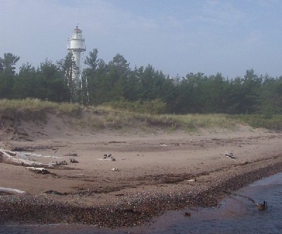 image along the coastline with the beach, trees, and lighthouse
