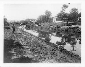 Black and white photograph, circa 1900, showing the Chesapeake and Ohio Canal operation in Hancock, MD.  Canal Company boat is being towed.  Various warehouses visible in photo.  Original iron bridge, crossing the canal is in background.