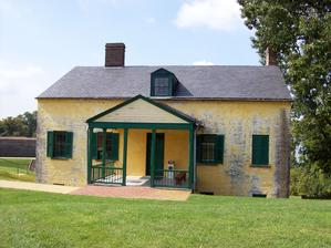 This exterior north view of the Commandant's House shows porch and main entrance to the Visitor Center that will be repaired.  The three HVAC unit are located under this porch.