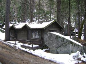 Photo of a cabin in Curry Village in the winter surrounded by snow and large rocks.