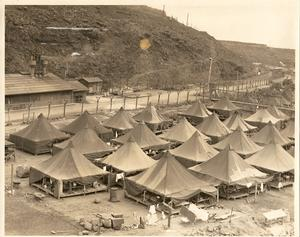 A photo of the historic Honouliuli site with makeshift tents set at the base of a hill next to a dirt road. Photo courtesy of Hawai'i's Plantation Village.