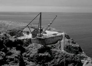 Black and white aerial photo of the historic derrick crane on the upper landing of Anacapa Island.