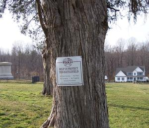 "A line of cedar trees at Harris Farm, Spotsylvania Courthouse battlefield, Virginia.  A battle monument at left midground. Recently-constructed estate home at right background.  A rectagular metal sign tacked to the nearest tree reads: ""APCWS--Help us protect this battlefield."""