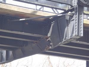 Photograph of the damaged bridge components.  Damage to a support beam.  Damage occured when the bridge was struck by an oversized vehicle.  Steel beam is cracked and bent longitudinally.