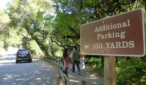 "Sign along Muir Woods road stating ""Additional Parking 100 yards"" with a view of the road and two pedestrians walking along the pathway."