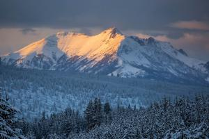 Sunlight hits the side of a snow-covered mountain in Yellowstone National Park
