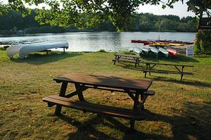Picnic table by the river with kayaks sitting on the banks with the sun setting.