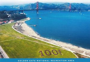 "Aerial photo displaying the west end of Crissy Field, the adjacent San Francisco Bay, and the Golden Gate Bridge, with the Marin Headlands behind it. A group of park visitors are arranged on the Crissy Field lawn to spell out ""100!""."