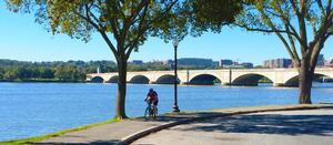 photo of a man on a bike on paved trail next to the Potomac River with Arlington Memorial Bridge in the background.