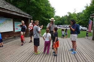 Image of an NPS staff providing information to children.