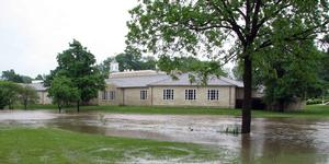 Photo of floodwaters swamp trees and approach the Presidential Library, 2008.