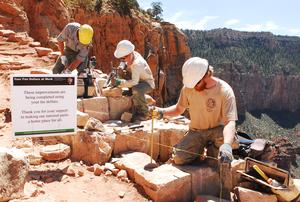 "Three workers rehabilitating a trail in Grand Canyon National Park using large rocks.  A sign by the trail states, ""These improvements are being completed using your fee dollars."""