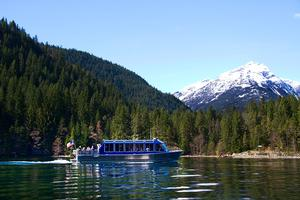 A photo showing a side view of the Alice Ross IV, a 55 foot, aluminum hulled, passenger boat, used for tours on Diablo Lake.  The boat has a silver hull and a blue passenger cabin with 6 dark tint windows on the side and skylights on the top.  People can be seen in the windows.  There is an open deck on the back of the boat with people gazing around at the landscape.  An American flag is attached to the stern of the boat.  The boat is captured moving to the right causing a gentle wake off its bow.  In the foreground are the shimmering waters of Diablo Lake.   In the mid-ground there is the rocky shoreline of the lake and forested hills with primarily coniferous trees.  In the background is the snow capped peak of Davis Mountain.  Photo courtesy of Seattle City Light.