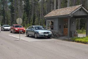 This photo depicts vehicles waiting in line to purchase an entrance pass at the south entrance of Crater Lake National Park.