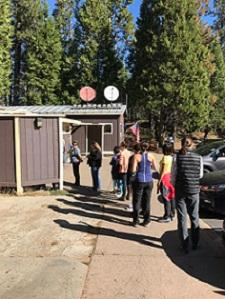 Photo of a typical day at the Big Oak Flat Visitor Contact Station; visitors experience waiting in a significant line at the restroom.