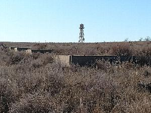 Concrete barracks foundations step down a slight slope in dry grass with the reconstructed Amache water tower rising in the background.