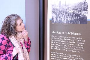 "A person looks at a museum exhibit panel containing a historic photo and text under the heading, ""Adventure or Fool's Mission?"""